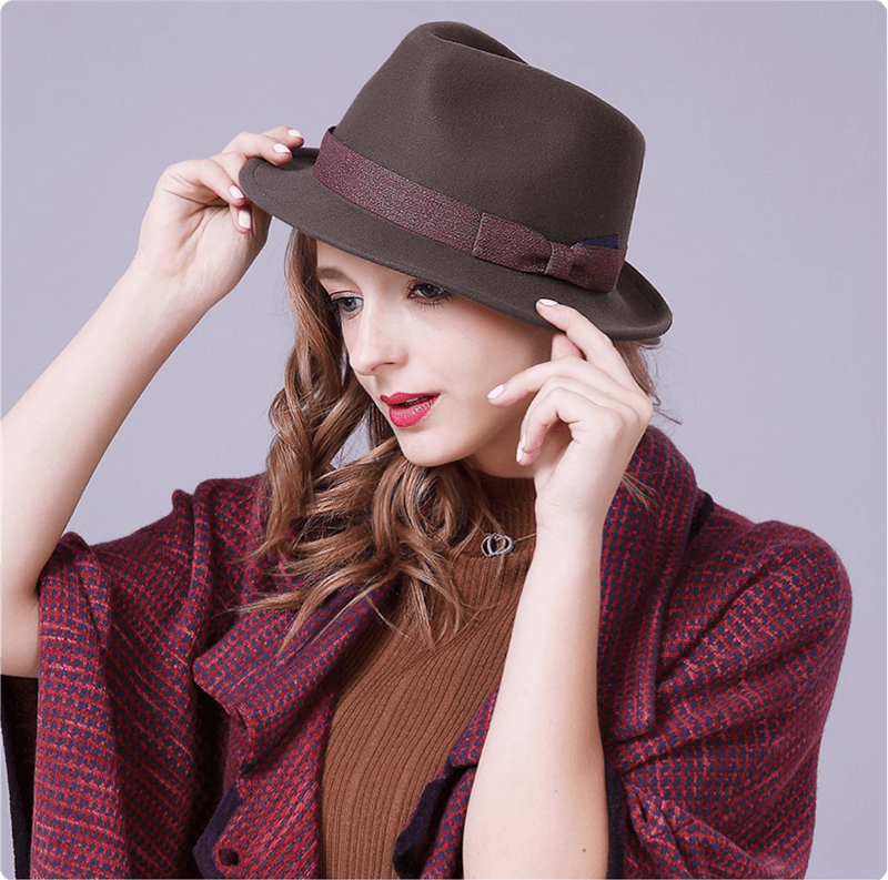Model settling her supreme trilby with two hands